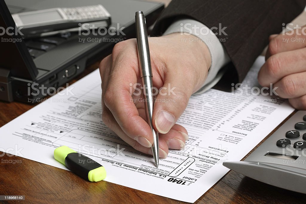 Close up of hand with pen filling out a tax form royalty-free stock photo