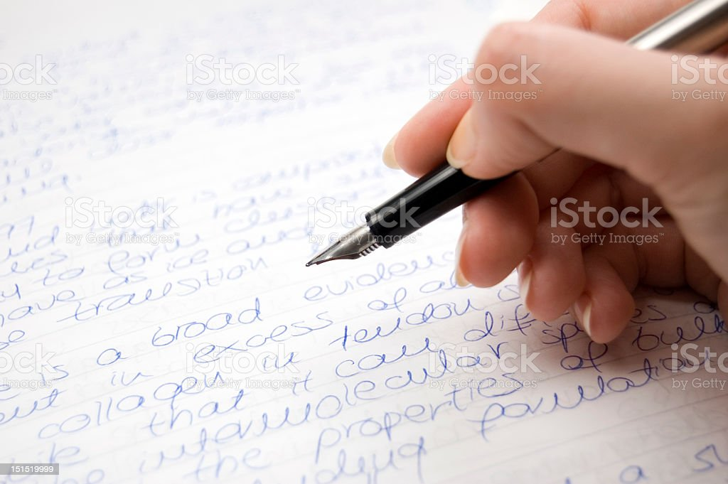 Close up of hand writing in pen on paper stock photo