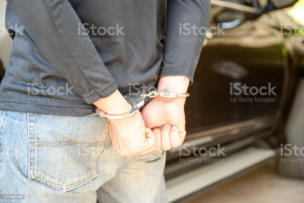Close up of handcuffed hands stock photo