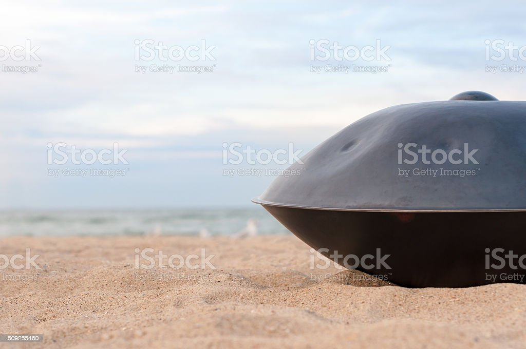 Close up of handpan or hang with sea and beach stock photo