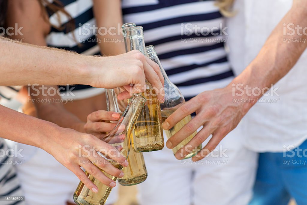 close up of hands clinking bottles with drinks stock photo