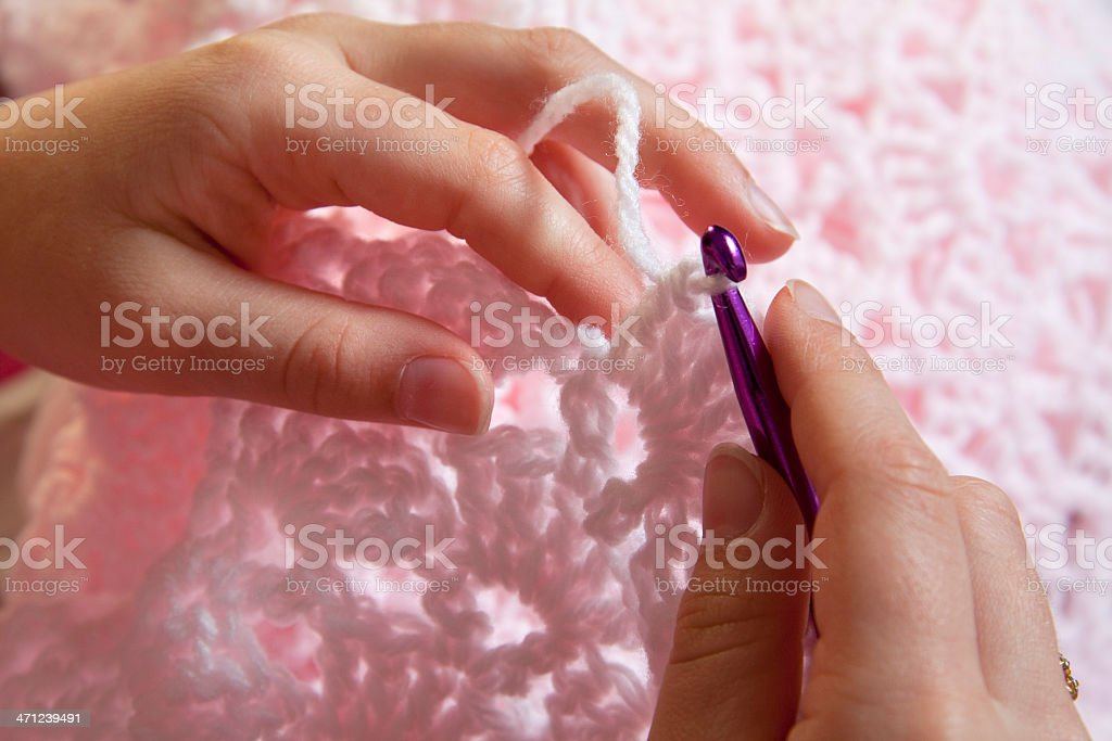 Close up of hands crocheting a pink baby blanket royalty-free stock photo