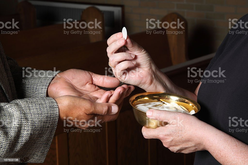 Close up of hands giving Communion stock photo