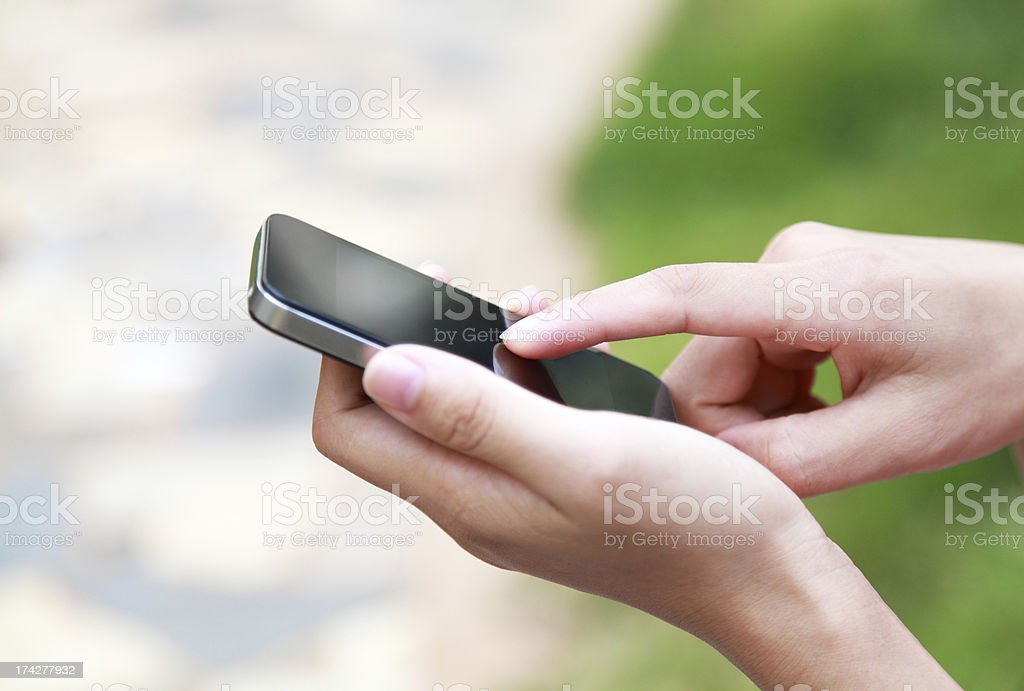 A close up of hands holding a black smart phone royalty-free stock photo