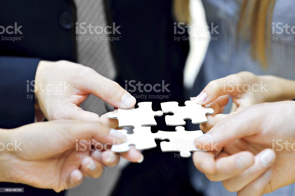 Close up of hands holding puzzle pieces stock photo