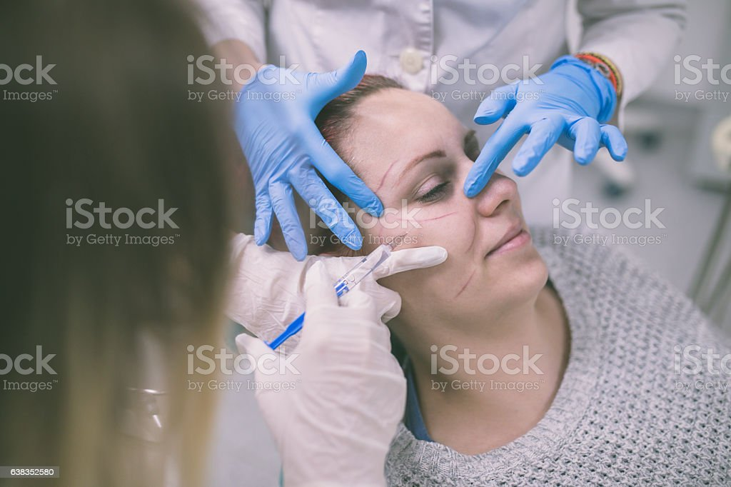 Close up of hands of cosmetologist making botox injection stock photo