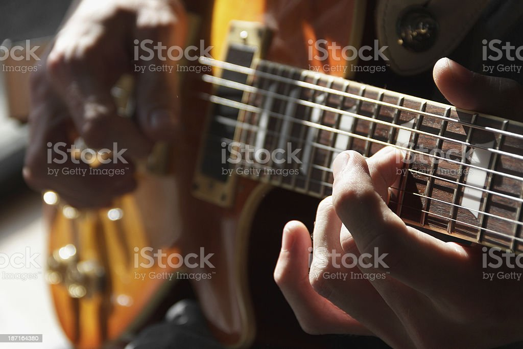 Close up of hands playing an electric guitar stock photo
