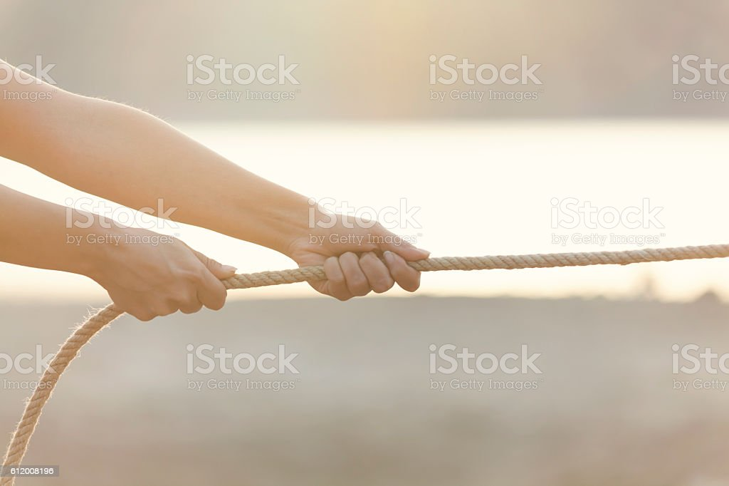 close up of hands pulling a rope stock photo