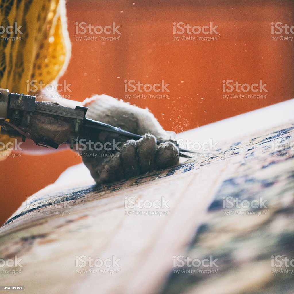 Close up of hands trimming a carpet stock photo