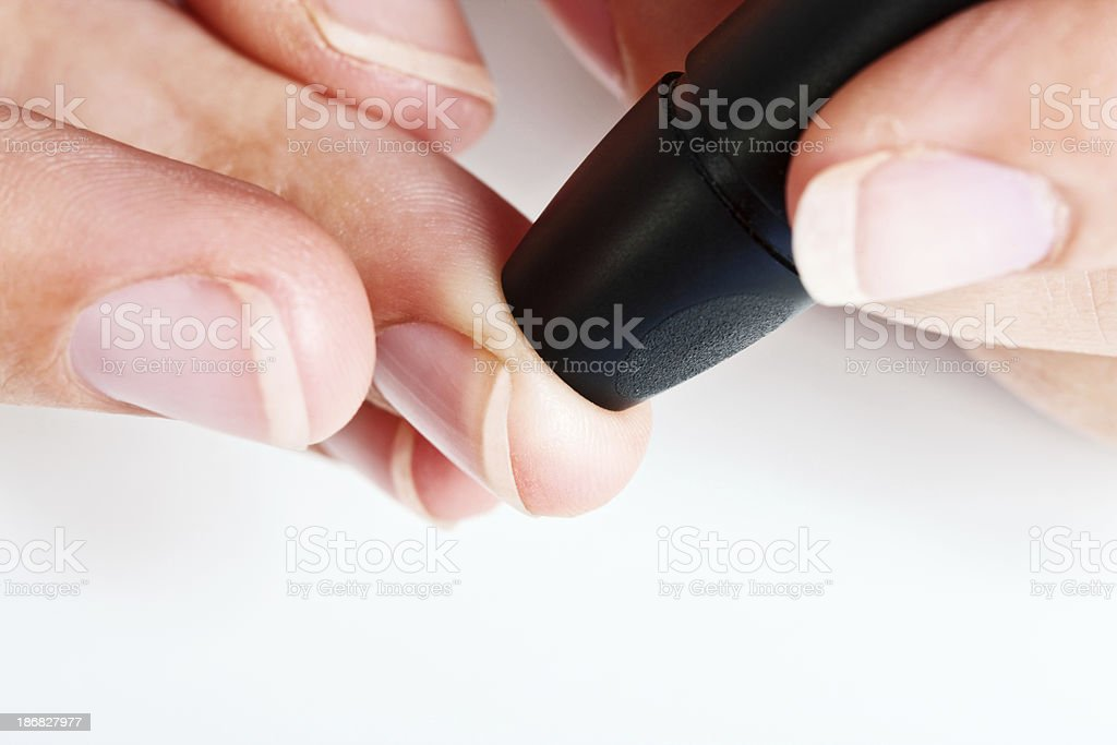 Close up of hands using automated lancet to draw blood stock photo