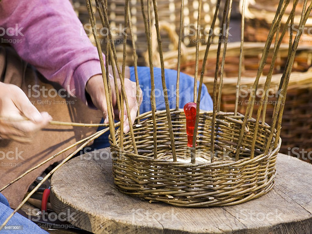 Close up of hands weaving a wicker basket stock photo