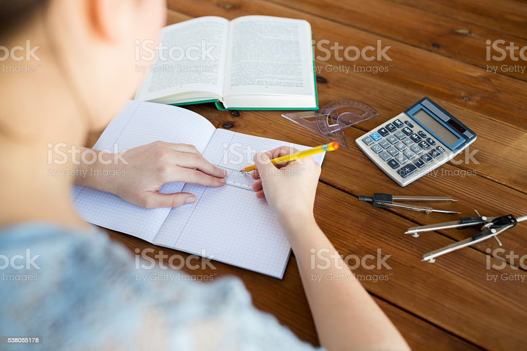 close up of hands with ruler and pencil drawing stock photo