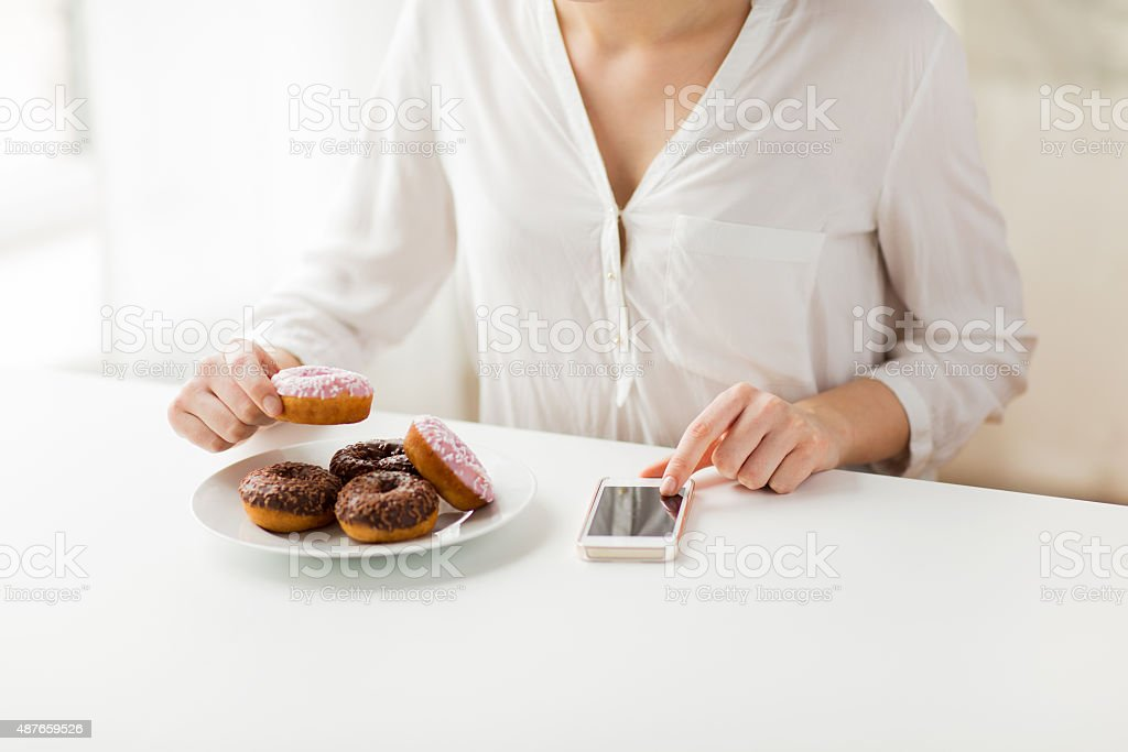 close up of hands with smart phone and donuts stock photo