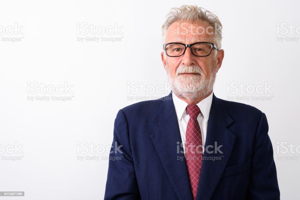 Close up of handsome senior bearded businessman wearing eyeglasses against white background stock photo