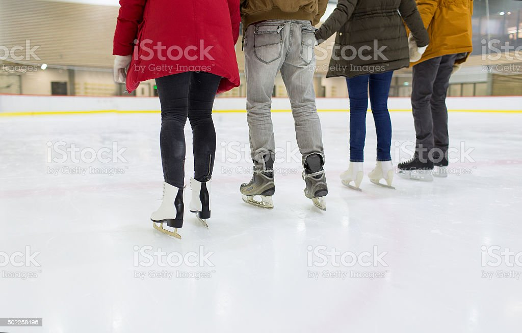 close up of happy friends skating on ice rink stock photo