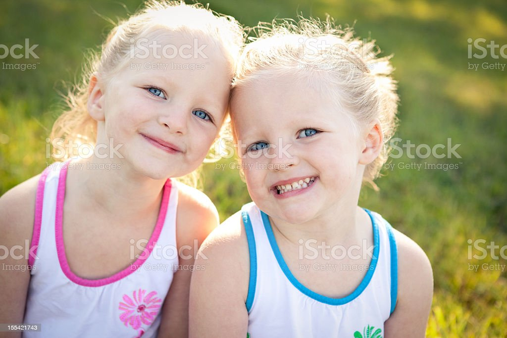 Close Up of Happy Little Twin Girls Sitting Together Outside royalty-free stock photo