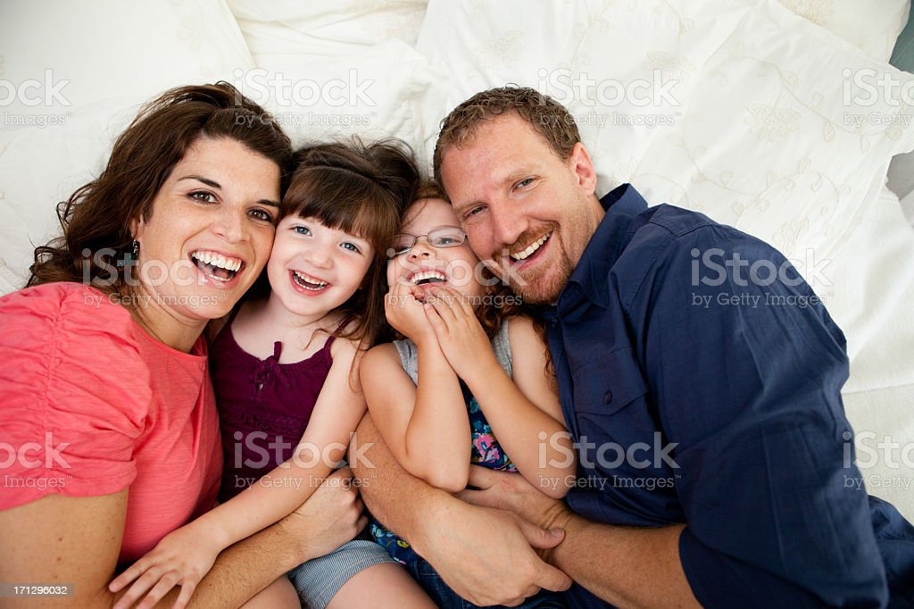 Close Up of Happy Sisters Cuddling With Dad and Mom royalty-free stock photo