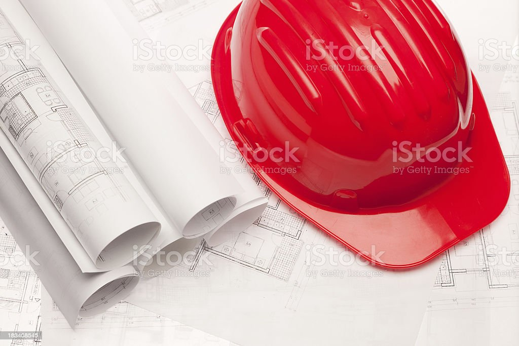 Close up of hard hat, pencil, measuring tape and blueprints stock photo