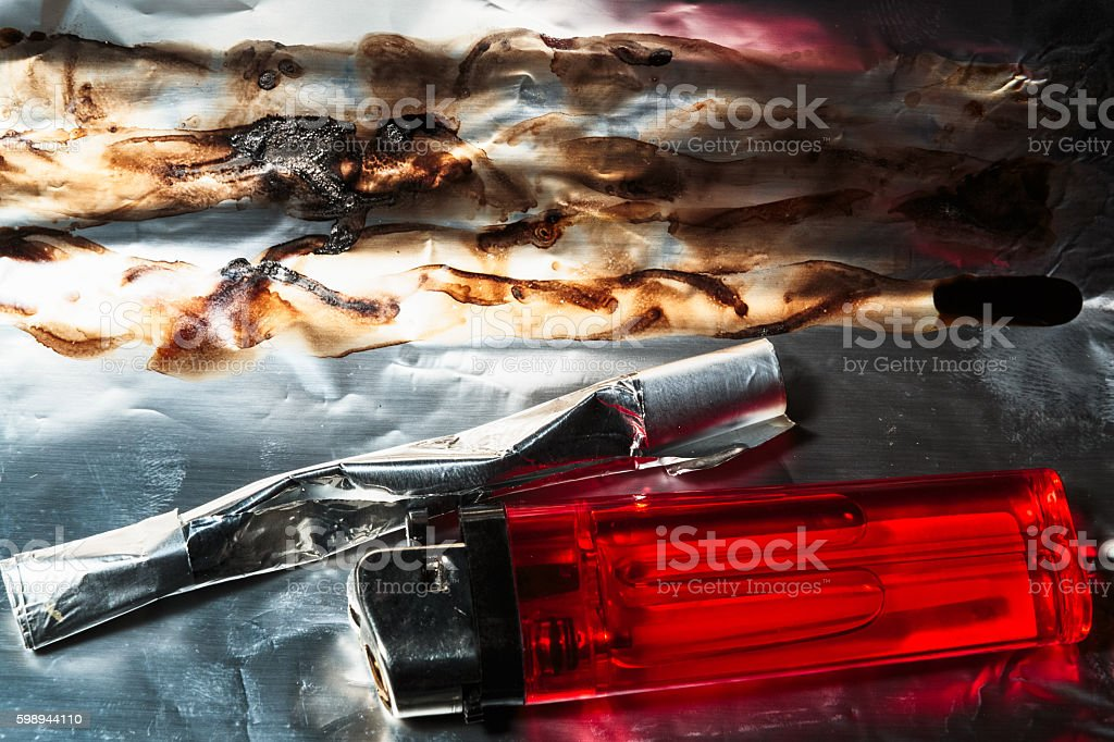 Close up of heroin on foil with lighter and tube stock photo