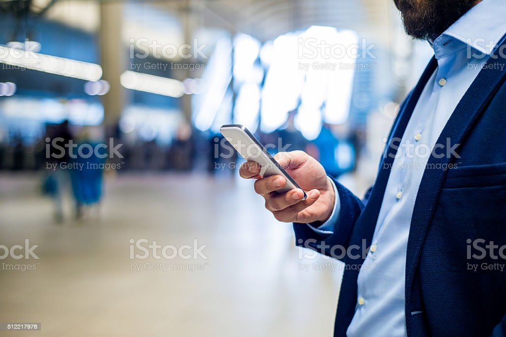 Close up of hipster businessman with smartphone, subway station stock photo