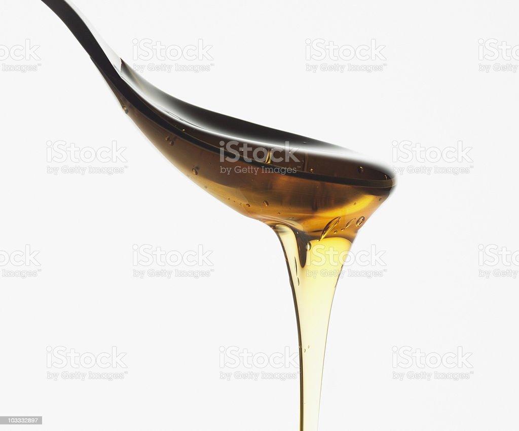 Close up of honey dripping from spoon stock photo