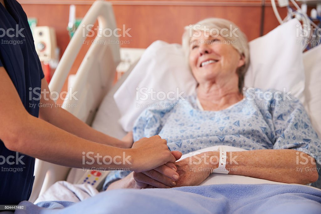 Close Up Of Hospital Nurse Holding Senior Patient's Hand stock photo