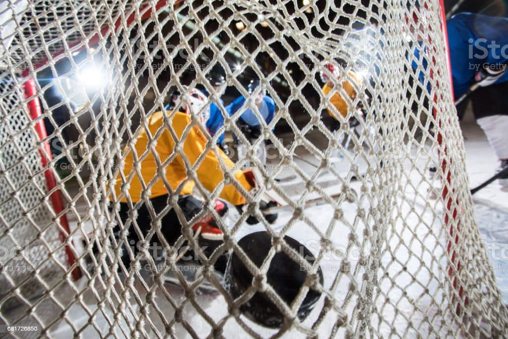 Close up of ice hockey goalkeeper's net with hockey puck in it. stock photo