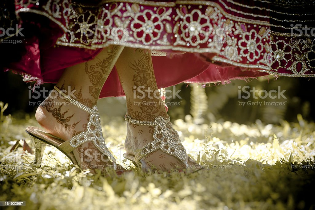 Close up of Indian bride's shoes dancing on green grass stock photo