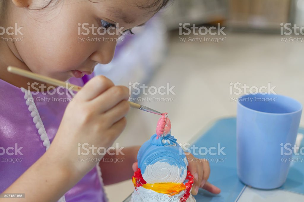 Close up of  kid painting color on the plaster statue stock photo