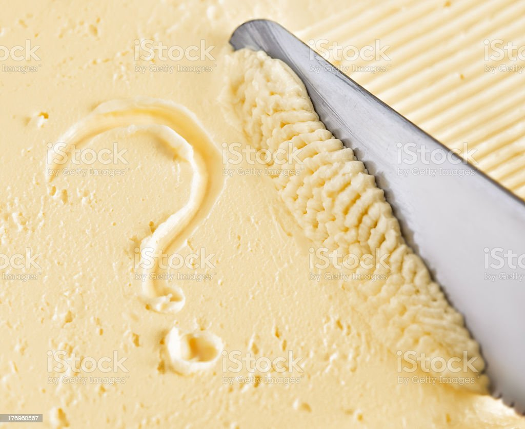 Close up of knife in butter with question mark drawn into it stock photo