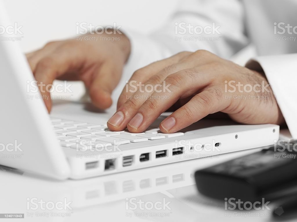 Close up of laptop with man typing on keyboard royalty-free stock photo
