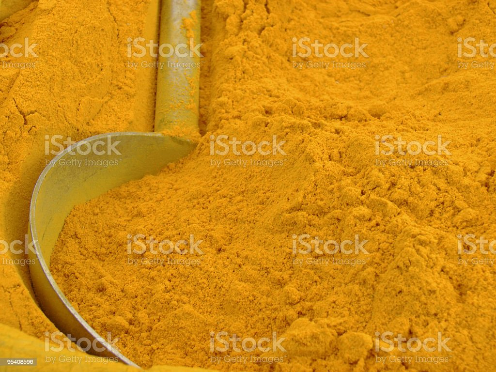 Close up of large spoon in pile of golden Indian turmeric  royalty-free stock photo
