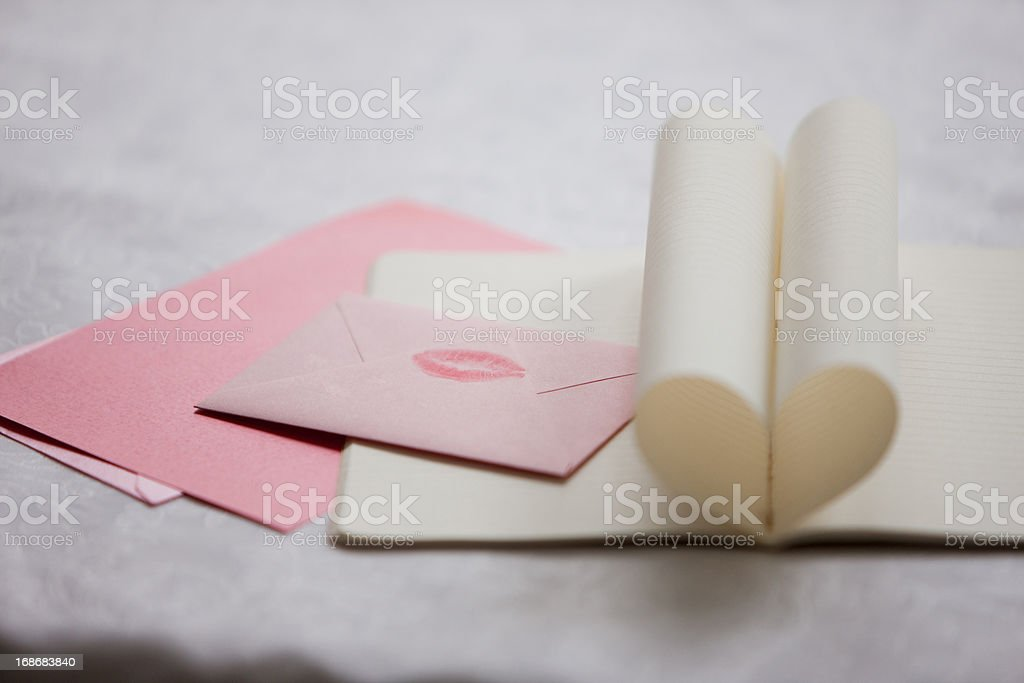 Close up of lipstick kiss on envelope and pages of notebook forming heart-shape stock photo