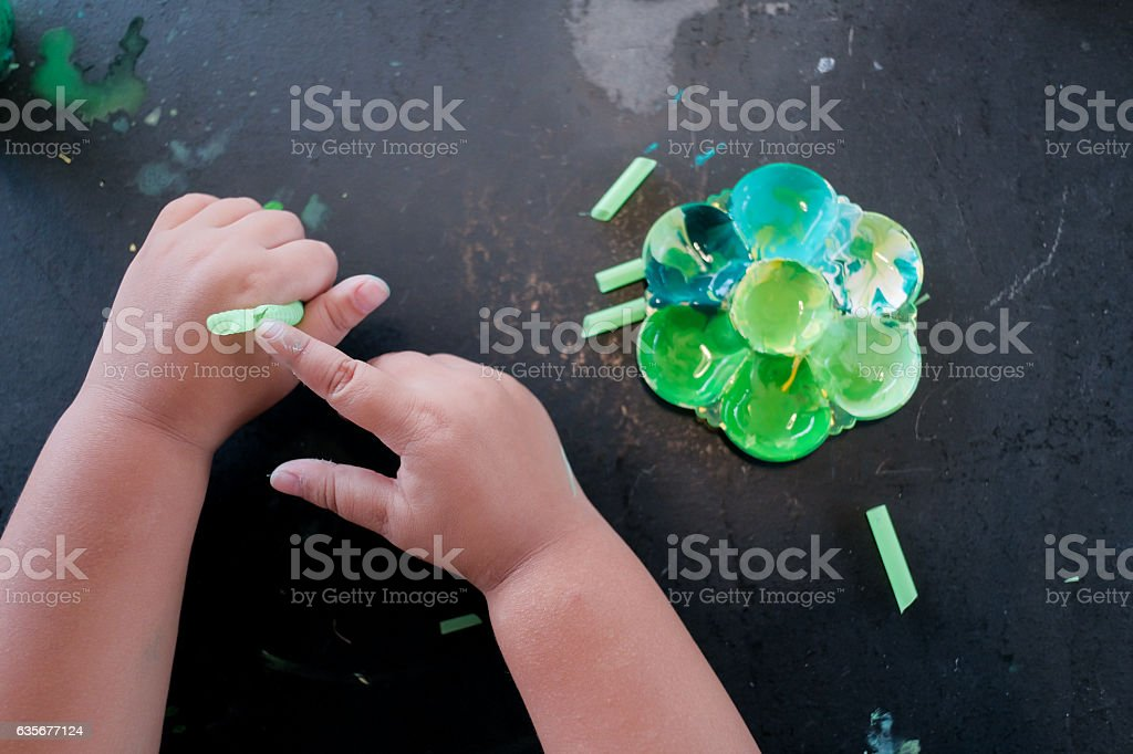 Close up of little child playing with fingerpaint colors. stock photo