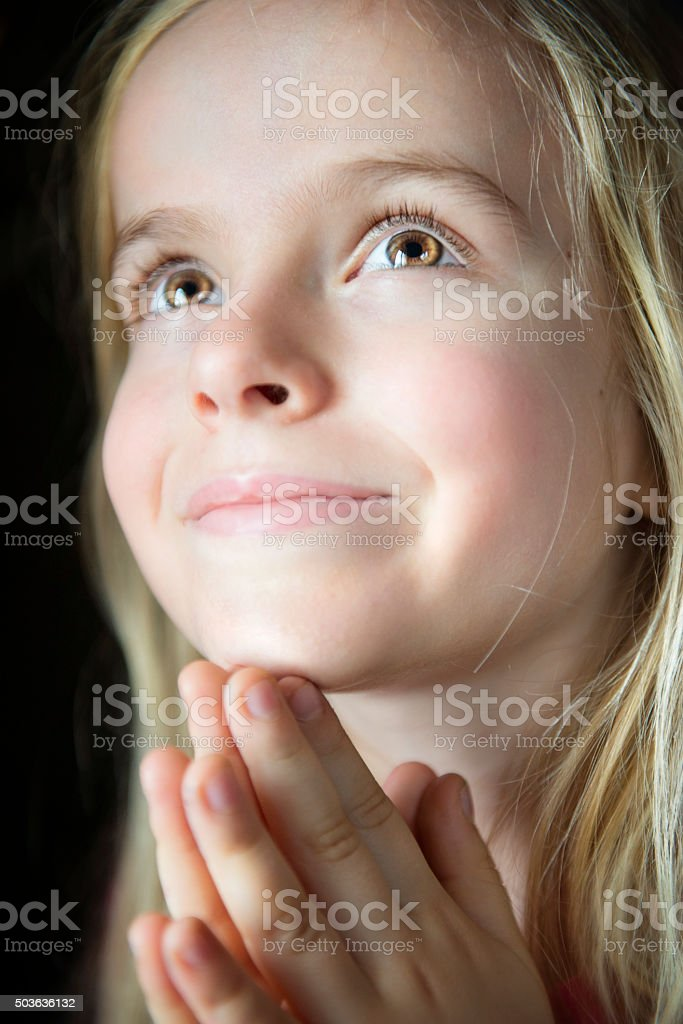 Close Up of Little Girl Praying. stock photo