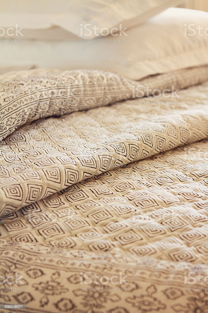 Close up of luxury quilt and pillow in background stock photo