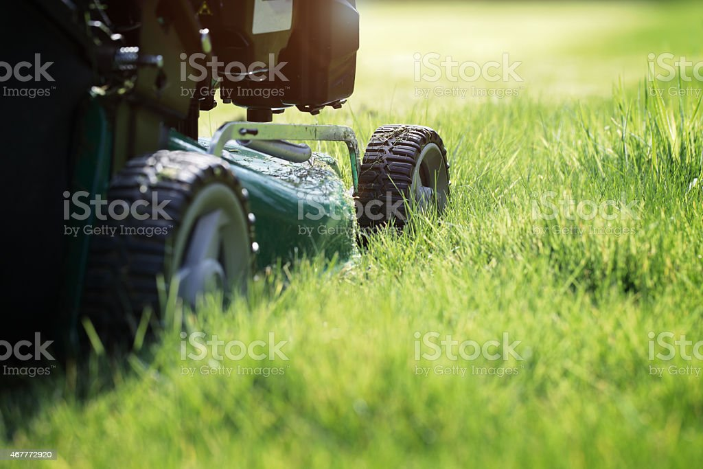 Close up of machine mowing grass stock photo