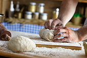 Close up of male baker hands kneading dough
