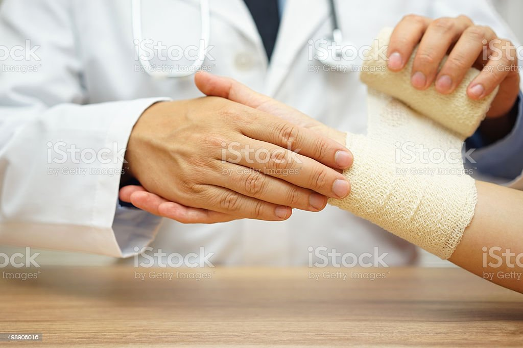 close up of male doctor bandaging female hand stock photo