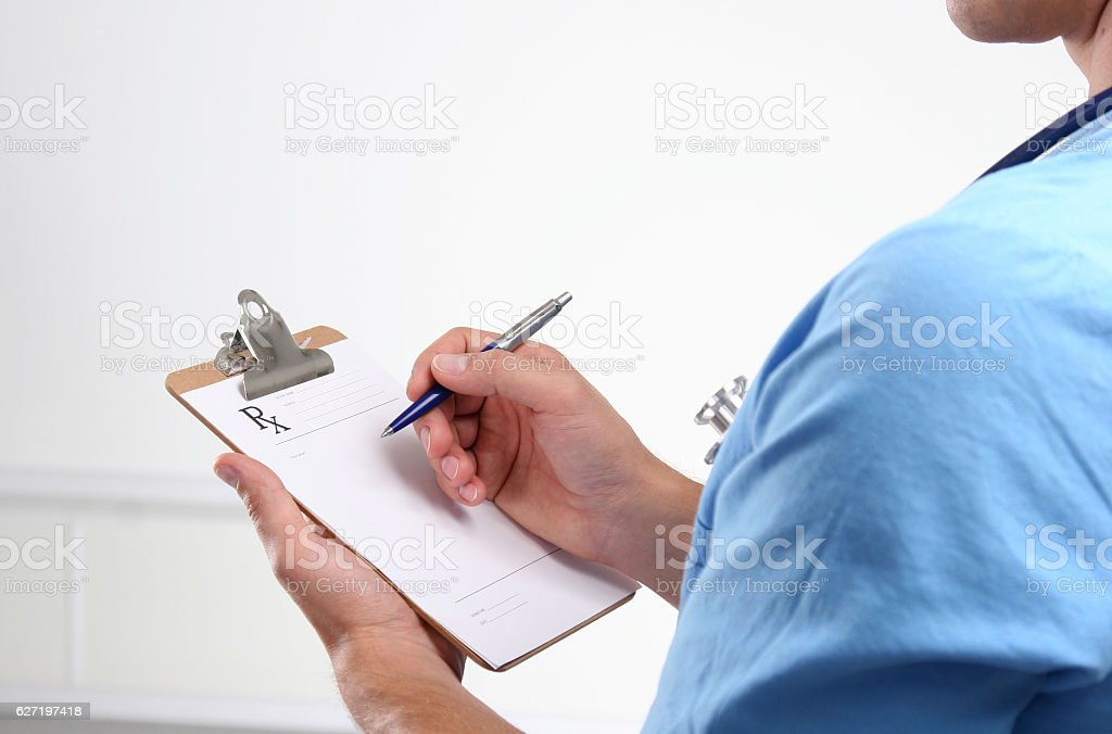 close up of male doctor writing prescription paper stock photo
