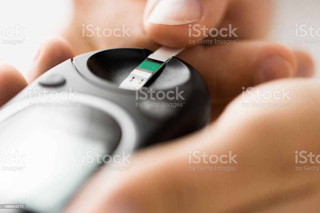 close up of man checking blood sugar by glucometer stock photo