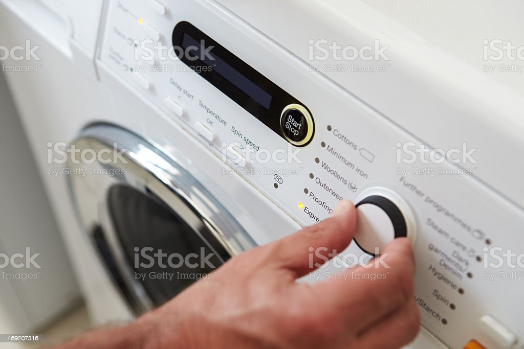 Close Up Of Man Choosing Cycle Program On Washing Machine stock photo