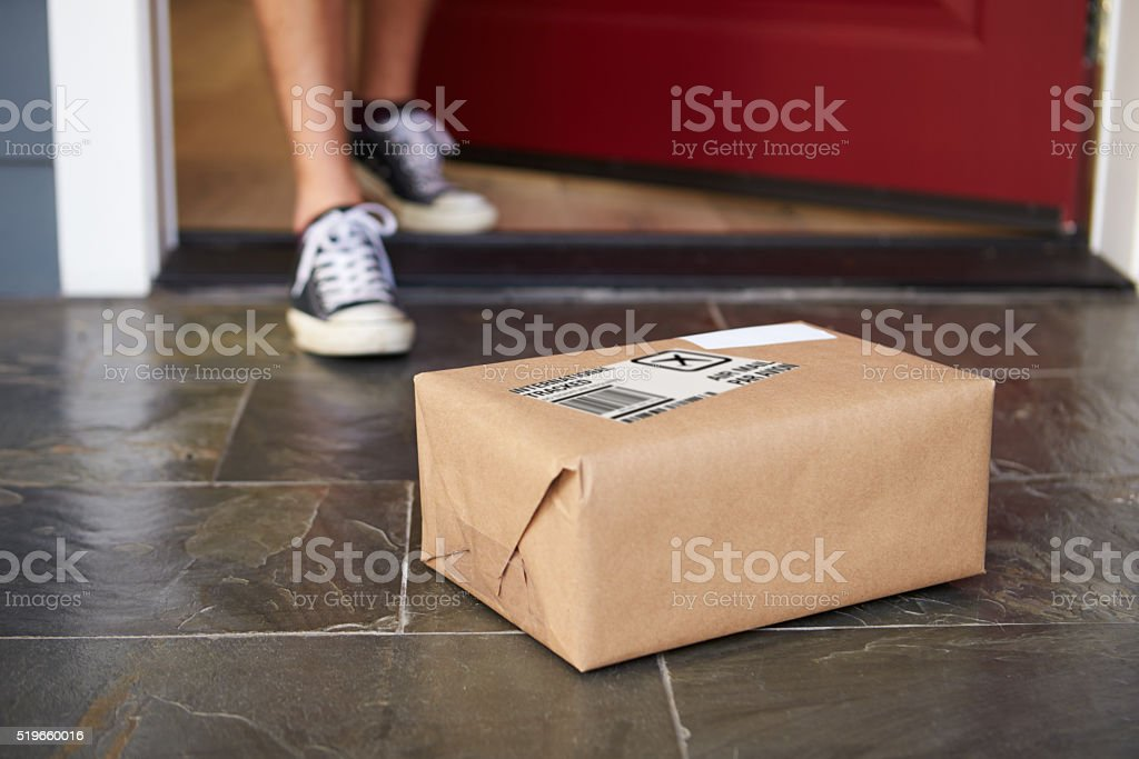 Close Up Of Man Collecting Parcel Delivery Outside Door stock photo