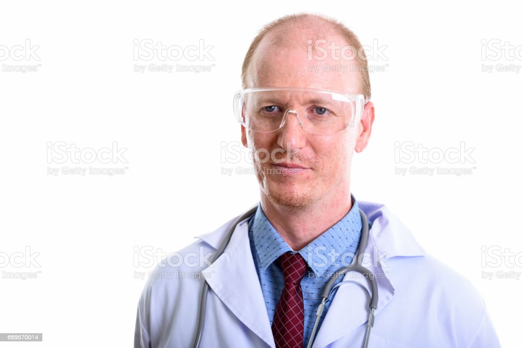 Close up of man doctor thinking while wearing protective glasses stock photo