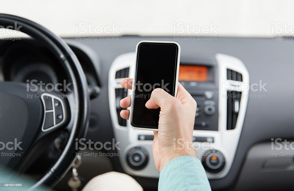 close up of man hand with smartphone driving car stock photo