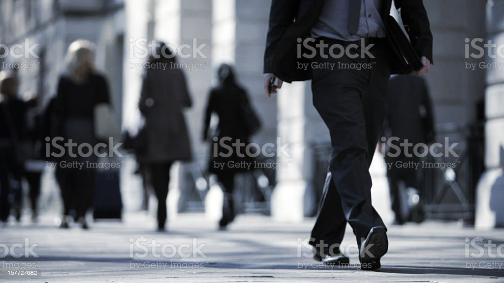 Close up of man in suit walking along busy street stock photo