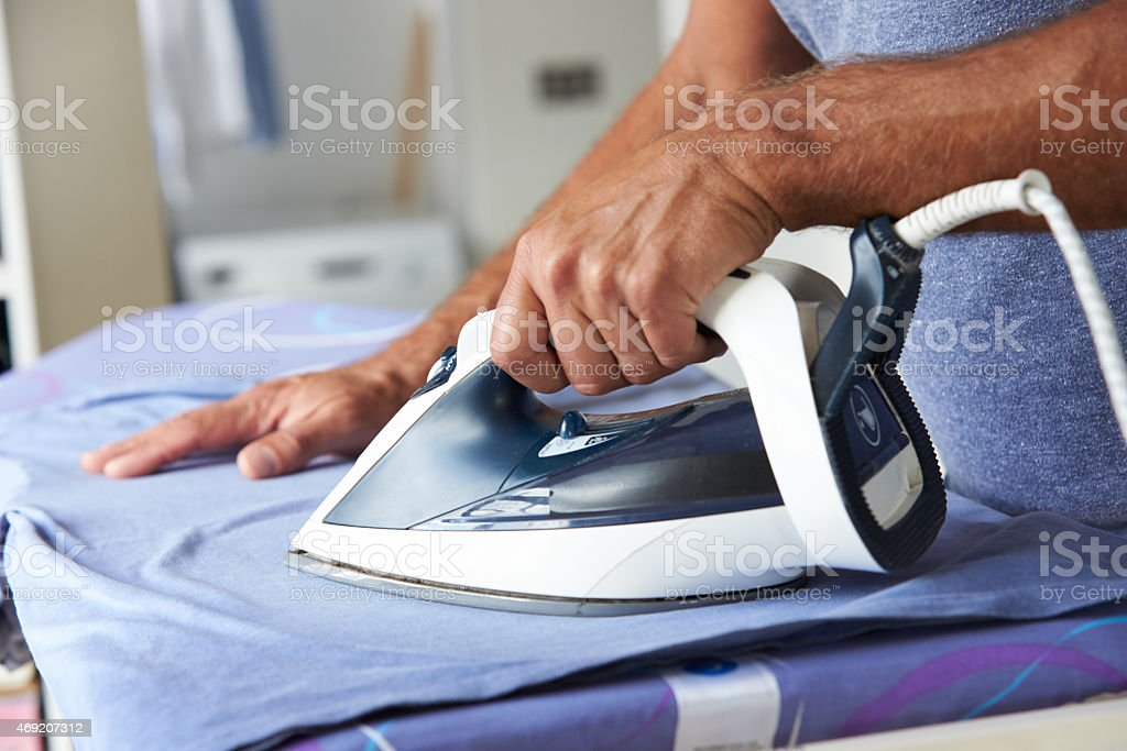 Close Up Of Man Ironing Laundry stock photo