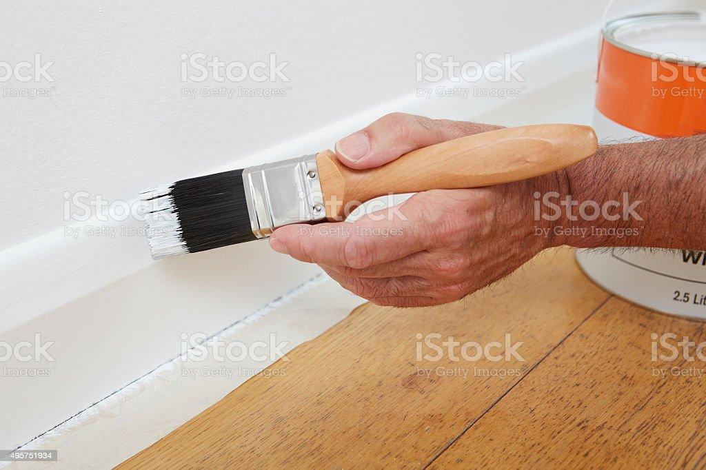 Close Up Of Man Painting Skirting Board stock photo
