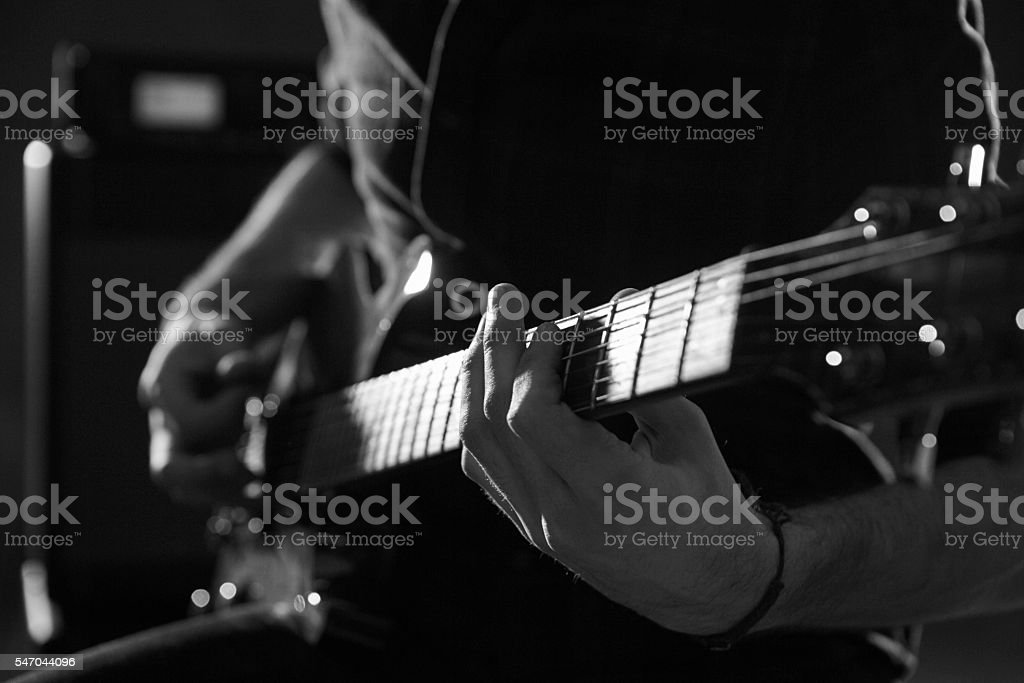 Close Up Of Man Playing Electric Guitar Shot In Monochrome stock photo