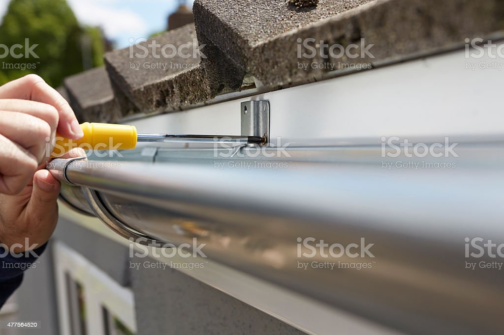 Close Up Of Man Replacing Guttering On Exterior Of House stock photo